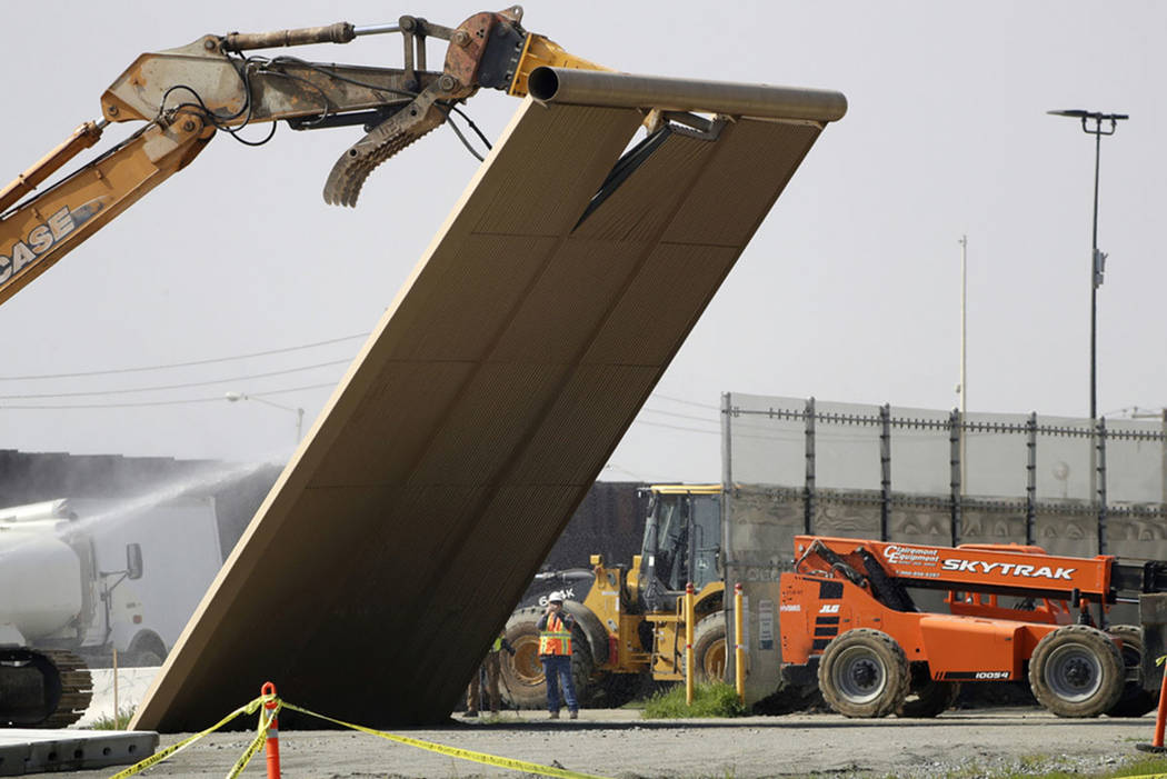 A border wall prototype falls during demolition at the border between Tijuana, Mexico, and San ...
