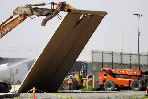 A border wall prototype falls during demolition at the border between Tijuana, Mexico, and San ...