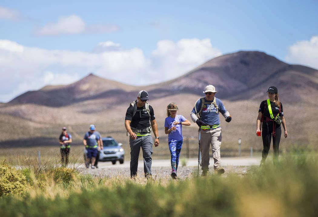Navy veteran Jelani Hale, of Las Vegas, from left, walks with daughter Jet, 9, retired civilian ...