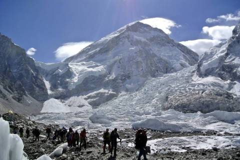 Climbers walk towards their helicopter (not seen) after their Mount Everest expeditions were ca ...