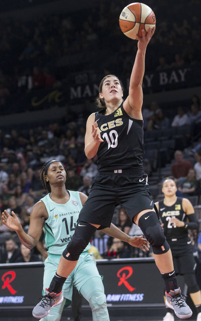 Aces guard Kelsey Plum (10) drives past New York Liberty guard Sugar Rodgers (14) in the first ...