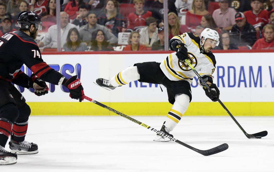 Boston Bruins' Brad Marchand (63) takes a shot on goal while Carolina Hurricanes' Jaccob Slavin ...