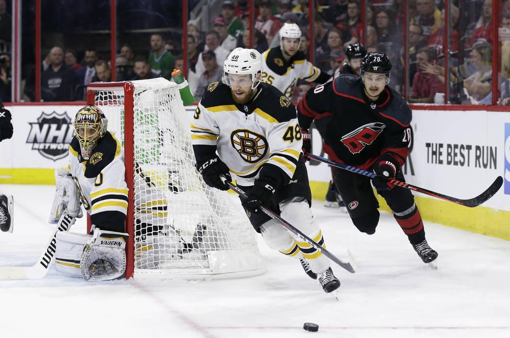 Boston Bruins' Matt Grzelcyk (48) controls the puck against a chasing Carolina Hurricanes' Seba ...