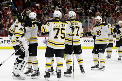 Boston Bruins goalie Tuukka Rask, left, of Finland, is congratulated by teammates following Gam ...