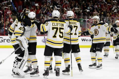 Boston Bruins goalie Tuukka Rask, left, of Finland, is congratulated by teammates following Gam ...