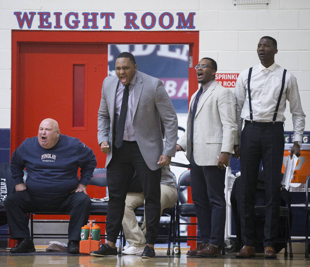 Findlay Prep head coach Rodney Haddix, second from left, reacts to a call during the Pilot's ho ...