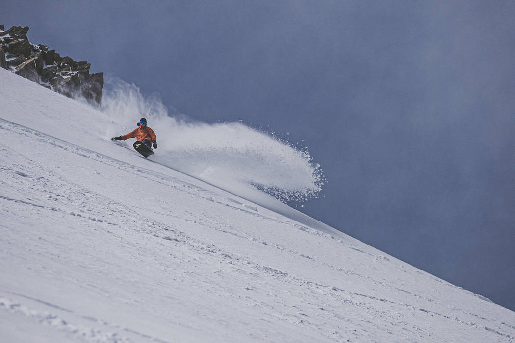 A snowboarder makes his way downhill in fresh snow at Mammoth Mountain ski area on May 17, 2019 ...
