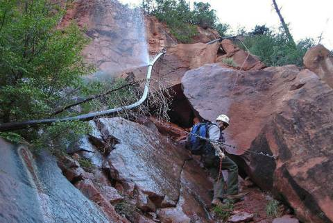A water sprays from a break in an exposed section of the Grand Canyon trans-canyon waterline as ...