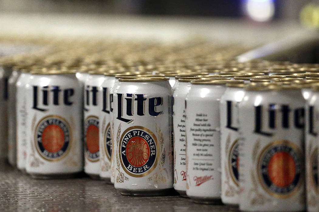 In this March 11, 2015 file photo, newly-filled and sealed cans of Miller Lite beer move along ...