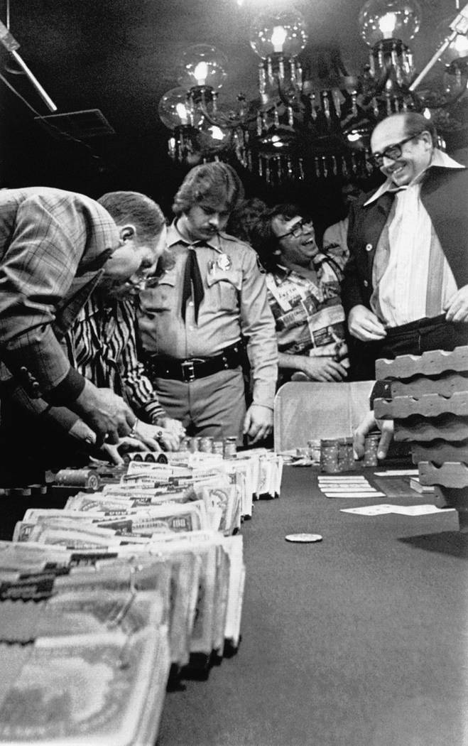"""""""Dolly"""" Doyle Brunson, right, of Fort Worth, Texas, looks at a trail of $100 bills he just won ..."""
