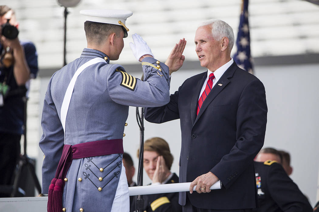 Vice President Mike Pence salutes a graduating cadet before handing him his diploma during grad ...