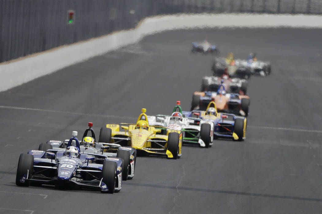 Ed Carpenter leads a group of cars into turn one during the final practice session for the Indi ...