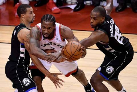 Toronto Raptors forward Kawhi Leonard (2) works between Milwaukee Bucks' George Hill, left, and ...