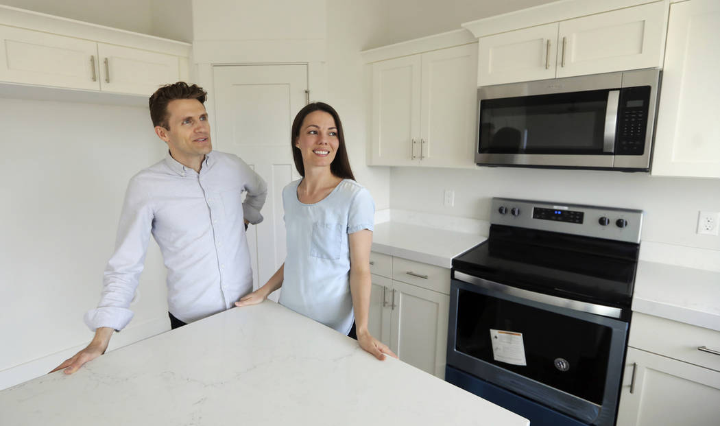 Andy and Stacie Proctor stand in their new home in Vineyard, Utah, in April 2019. (AP Photo/Ri ...
