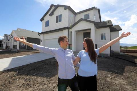 Andy and Stacie Proctor stand in front of their new home in Vineyard, Utah, in April 2019. (AP ...
