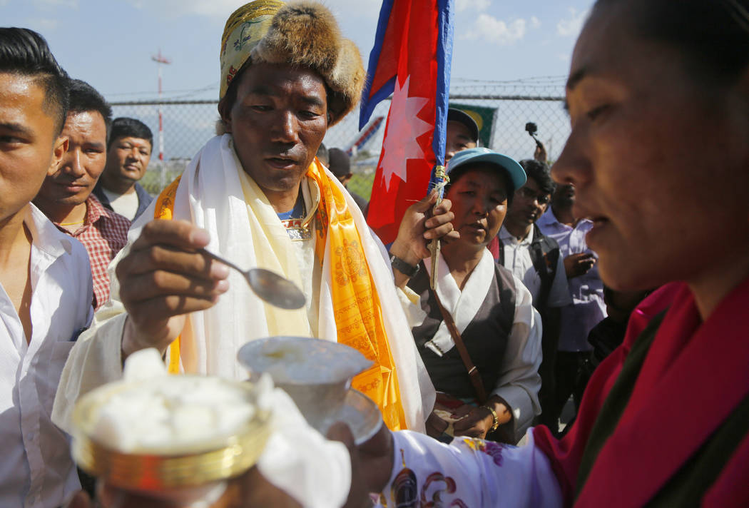Nepalese veteran Sherpa guide Kami Rita, 49, is welcomed by his wife at the airport in Kathmand ...