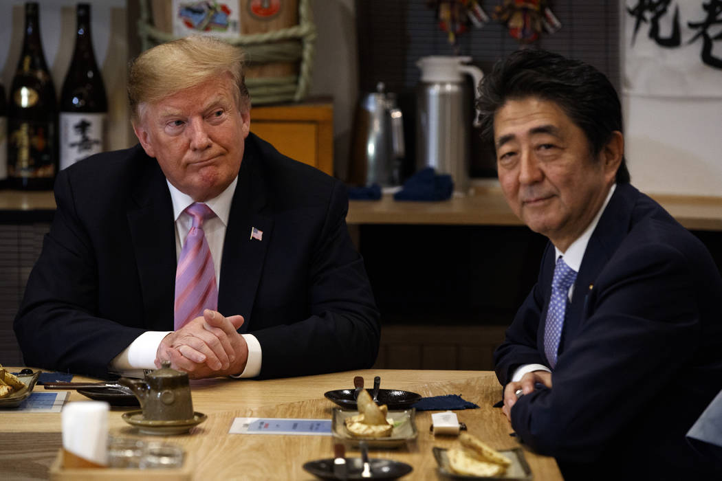 President Donald Trump sits at dinner with Japanese Prime Minister Shinzo Abe, Sunday, May 26, ...
