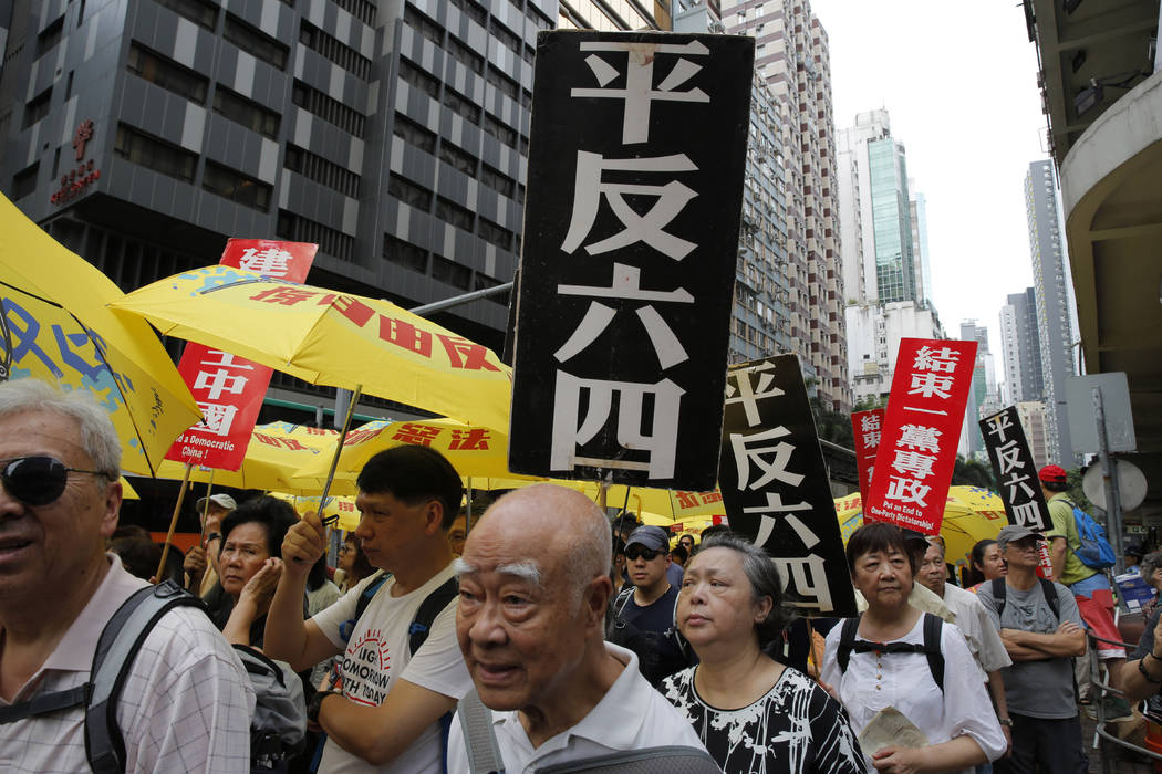 """Pro-democracy protesters carry placards with Chinese reads """"Vindicate June 4th"""" and & ..."""