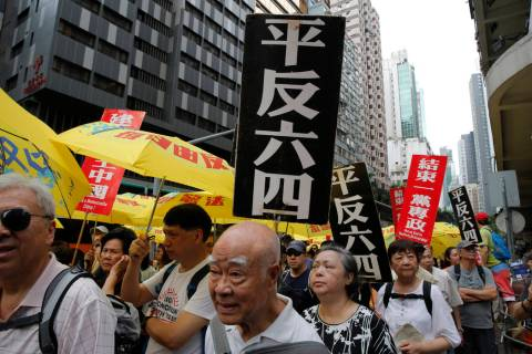 "Pro-democracy protesters carry placards with Chinese reads ""Vindicate June 4th"" and & ..."