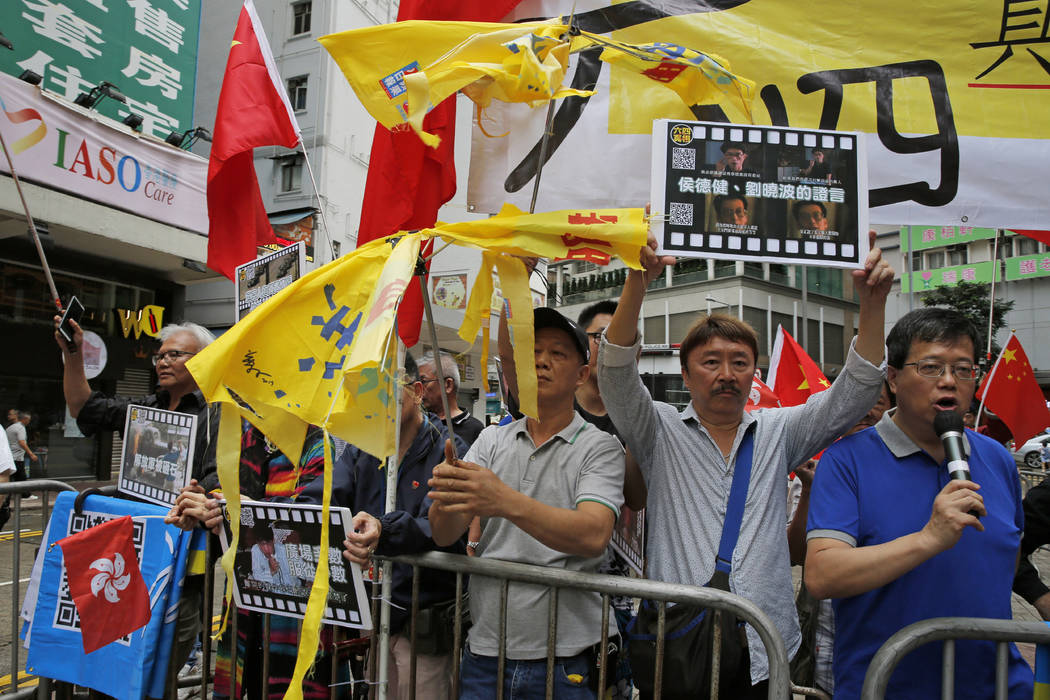 Pro-Beijing supporters destroy yellow umbrellas, used to mark protesting denouncing far-reachin ...