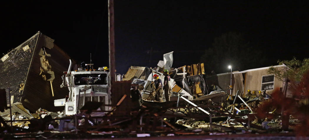 Emergency workers search through debris from a mobile home park, Sunday, May 26, 2019, in El Re ...