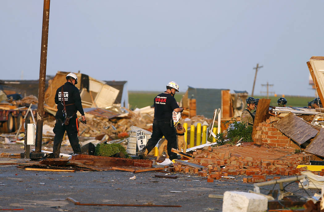 Workers look through tornado damage at the American Budget Value Inn in El Reno, Okla., Sunday, ...