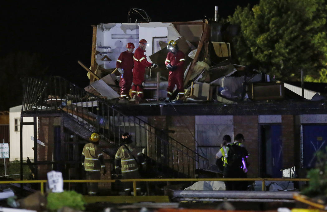 Emergency workers check what is left of the second floor of a hotel, Sunday, May 26, 2019, in E ...