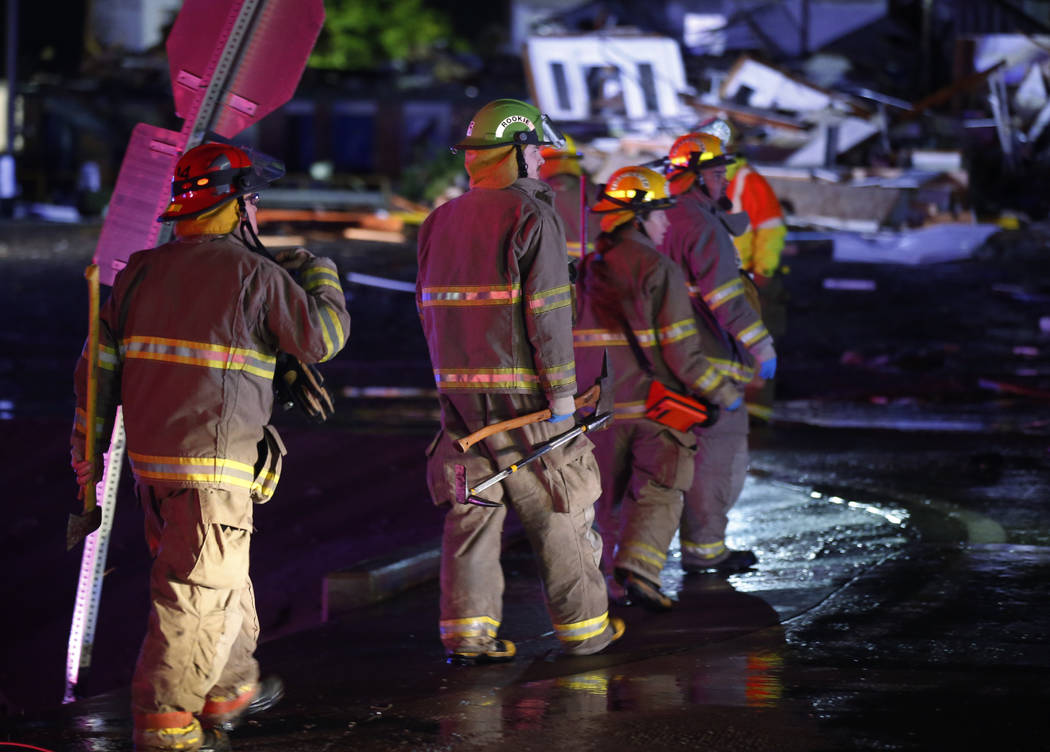Firefighters walk to an area of debris from a hotel and a mobile home park in El Reno, Okla., S ...