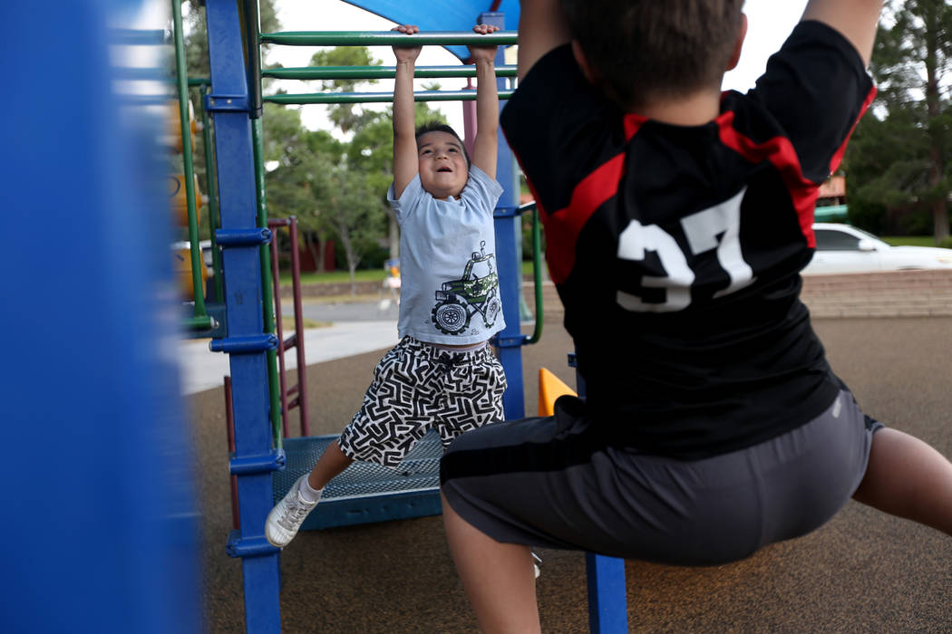 Alec Reyes, 5, climbs the monkey bars with his brother Eli Reyes, 10, right, at Bicentennial Pa ...