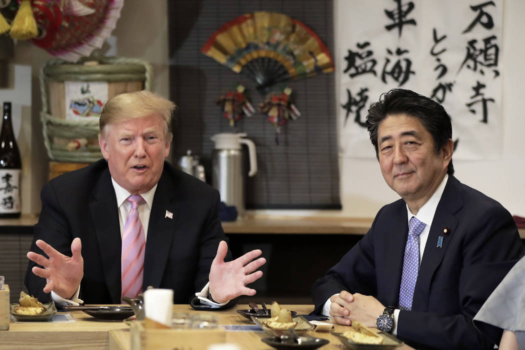 U.S. President Donald Trump, left, speaks as he dines with Japan's Prime Minister Shinzo Abe at ...