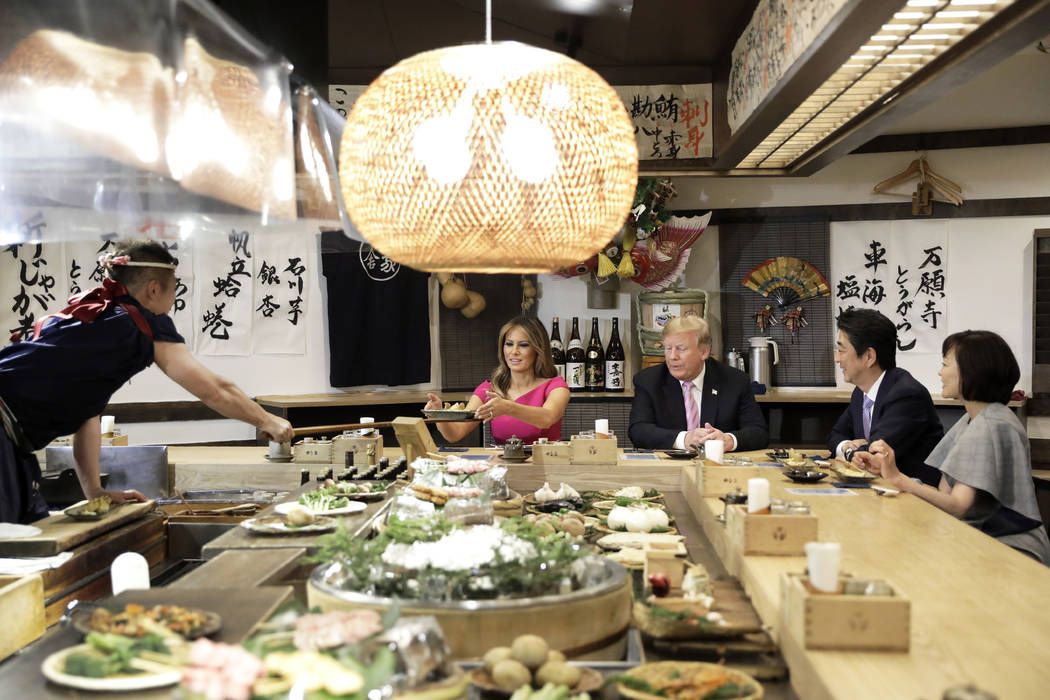 U.S. first lady Melania Trump, second left, is served a baked potato with butter while sitting ...