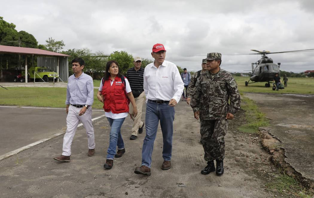 Peru's President Martin Vizcarra, second from right, arrives to the airport after checking eart ...