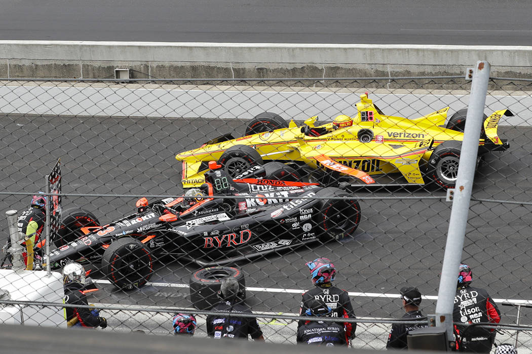 Helio Castroneves, of Brazil, rear, makes contact with James Davison, of Australia, during the ...