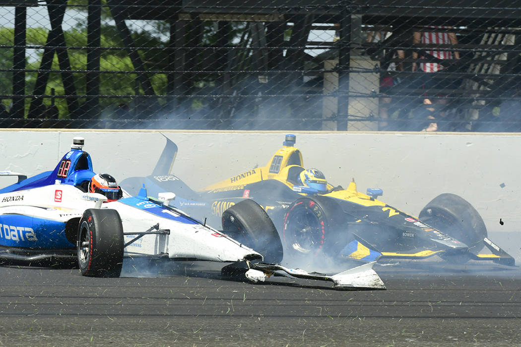 Felix Rosenqvist, of Sweden, left, and Zach Veach collide in the third turn during the Indianap ...