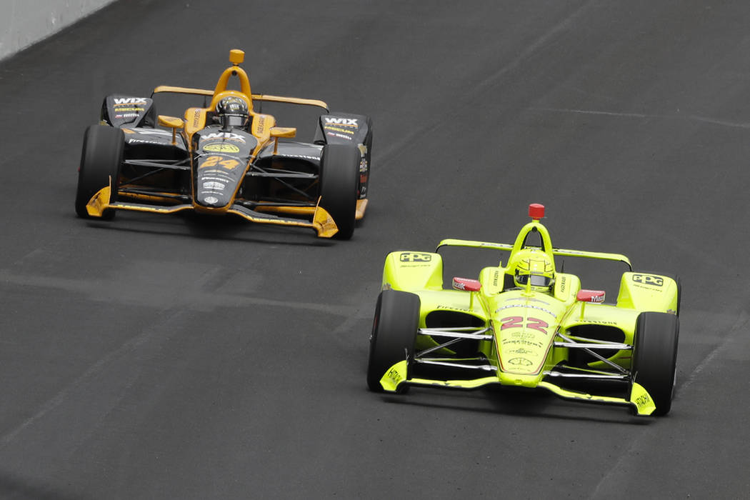 Simon Pagenaud, of France, leads Sage Karam into the first turn during the Indianapolis 500 Ind ...