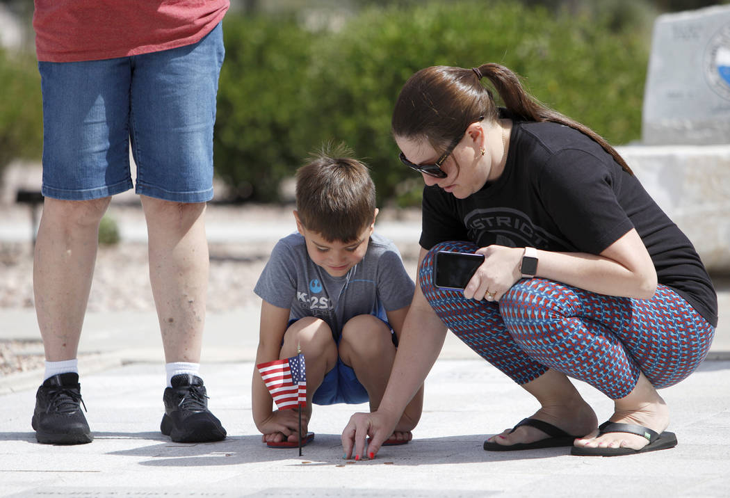 Sarah Vela helps her son Jace Vela, 5, place a flag on her grandfatherճ memorial stone at ...
