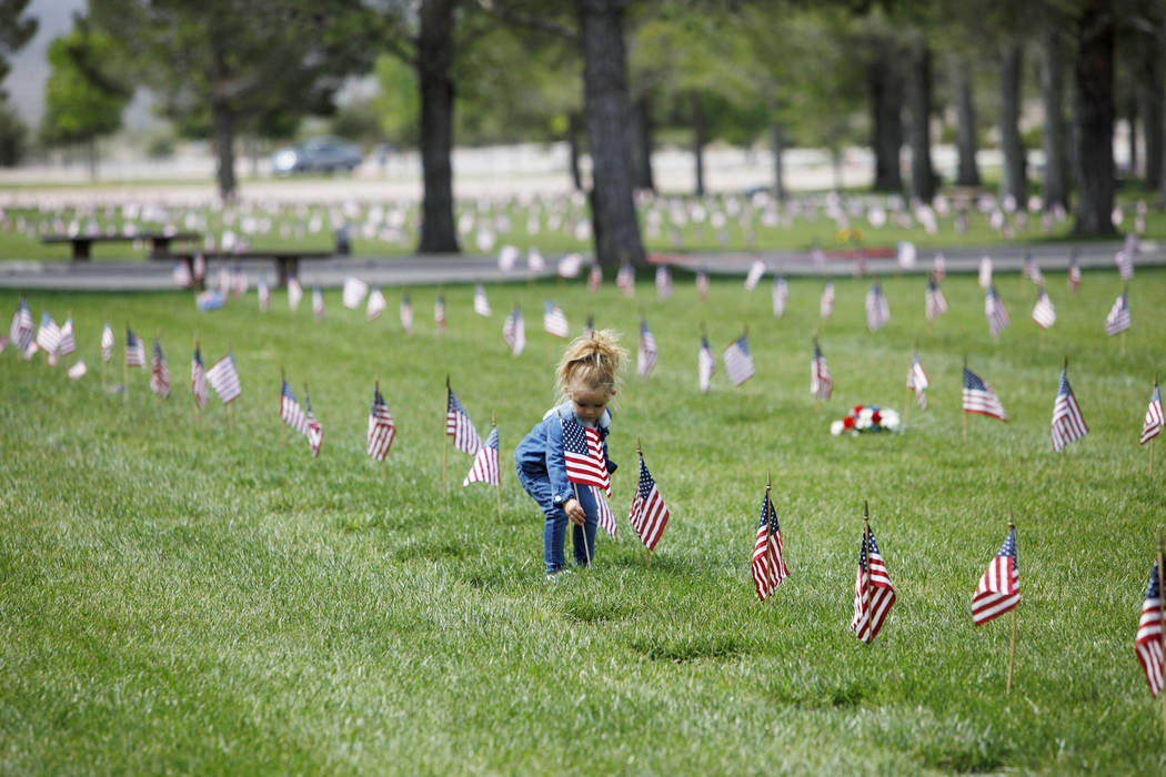 Liyah Makarechian, 3, places a flag at a headstone site at the Southern Nevada Veterans Memoria ...
