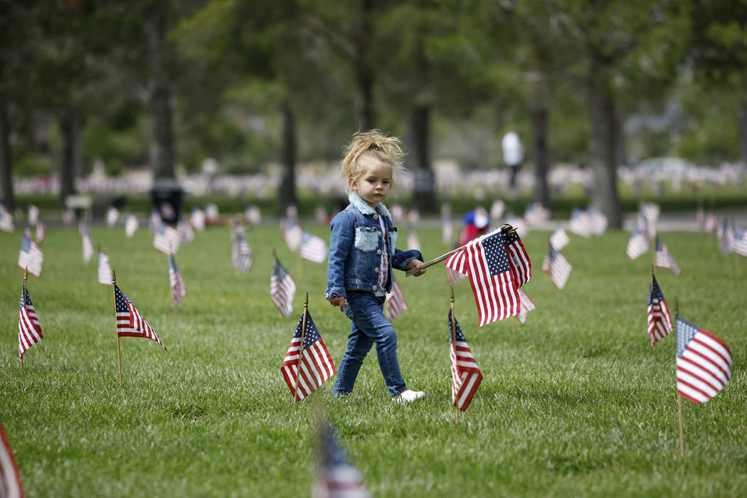 Liyah Makarechian, 3, wanders with a flag at the Southern Nevada Veterans Memorial Cemetery in ...