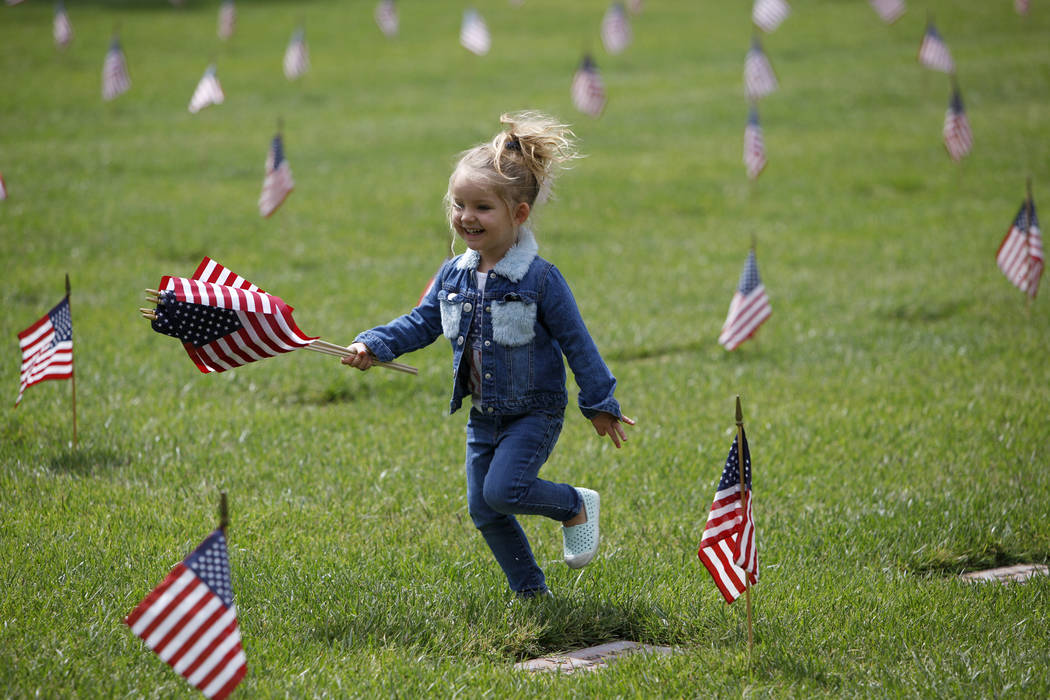 Liyah Makarechian, 3, runs with a flag at the Southern Nevada Veterans Memorial Cemetery in Bou ...