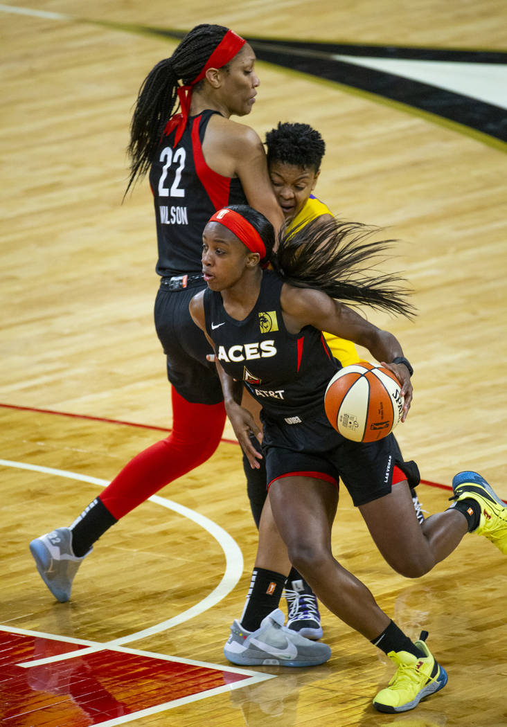 Las Vegas Aces guard Jackie Young (0) drives t6he lane past a pick by teammate center A'ja Wils ...
