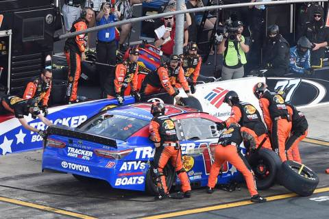 Crew members lift Martin Truex Jr.'s car to change a flat tire during a NASCAR Cup Series auto ...