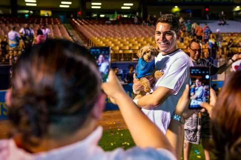 Las Vegas Lights FC goalkeeper Thomas Olsen (1) poses with dog Nessie for fan Ruby Castillo fol ...
