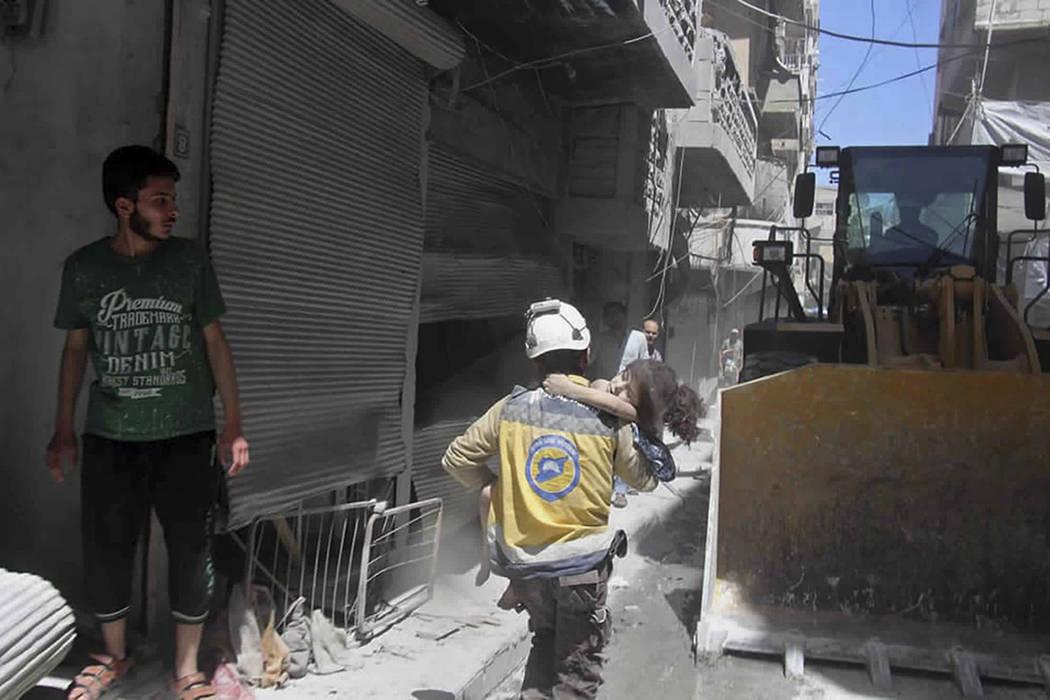 This photo provided by the Syrian Civil Defense White Helmets, which has been authenticated bas ...