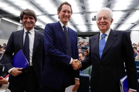 FCA Chairman John Elkann, center, shakes hands with former Italian Premier Mario Monti, right, ...