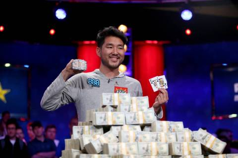 John Cynn holds his gold championship bracelet and winning hand after winning the World Series ...
