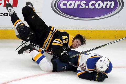 Boston Bruins' Torey Krug (47) and St. Louis Blues' Robert Thomas (18) crash to the ice during ...