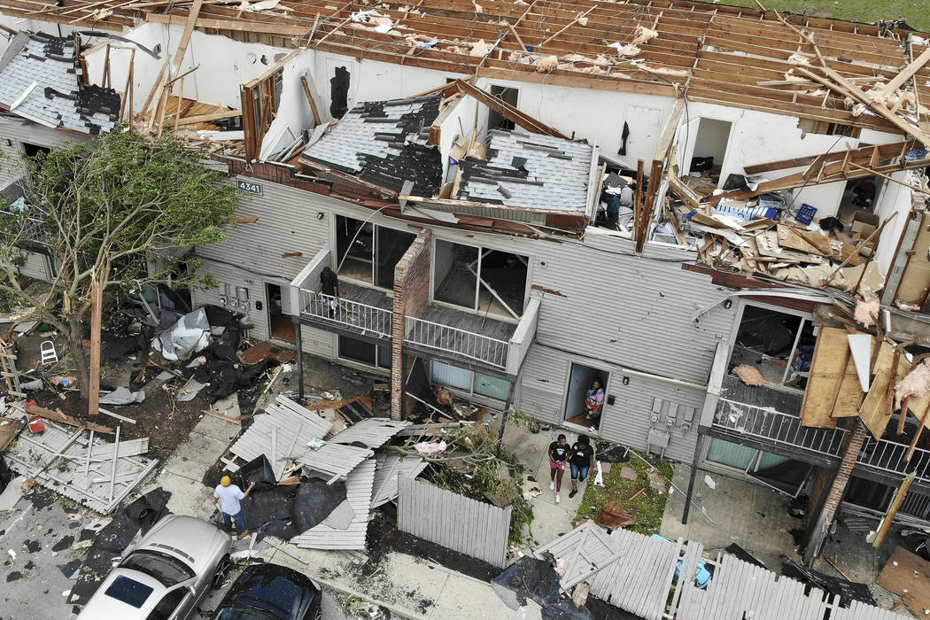 Residents and visitors walk through debris at the River's Edge apartment complex, Tuesday, May ...
