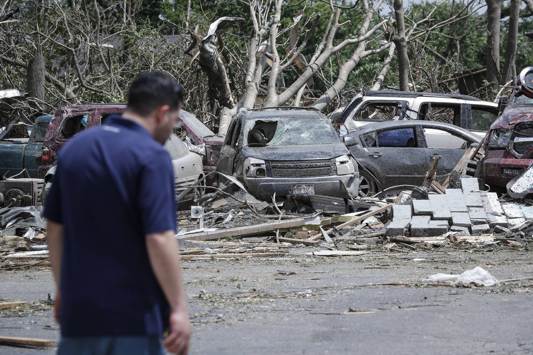 Pedestrians pass along storm debris on North Dixie Drive, Tuesday, May 28, 2019, in Dayton, Ohi ...