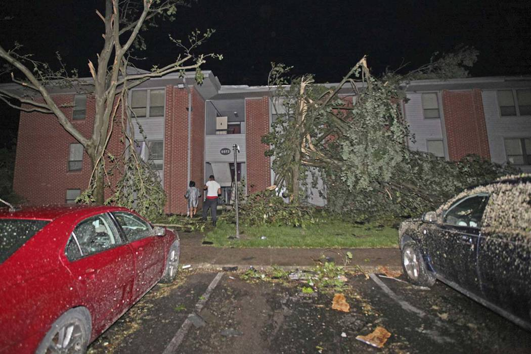Residents walk toward their Westbrooke Village Apartment building that was heavily damaged by a ...