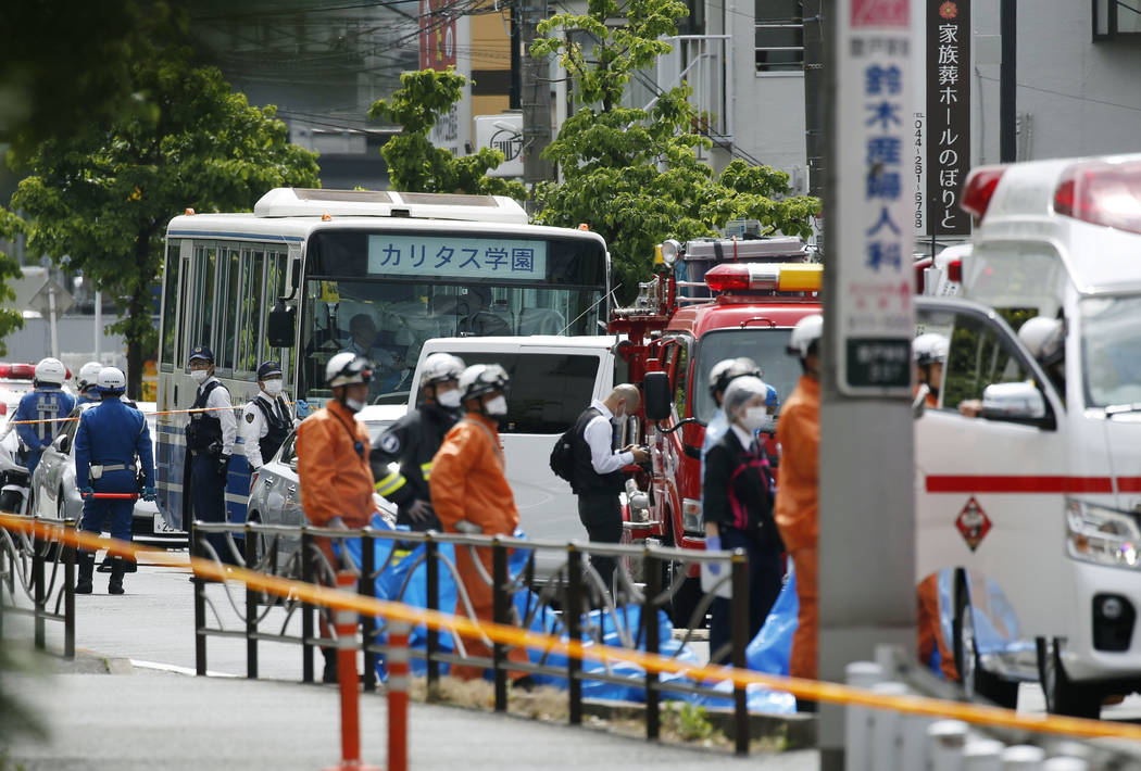 A school bus, center, is parked at the scene of an attack in Kawasaki, near Tokyo Tuesday, May ...